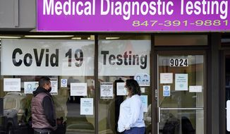 FILE - In this Oct. 21, 2020, file photo, Exam Corp Lab employee, right, wears a mask as she talks with a patient lined up for COVID-19 testing in Niles, Ill. The United States is approaching a record for the number of new daily coronavirus cases in the latest ominous sign about the disease's grip on the nation. (AP Photo/Nam Y. Huh, File)