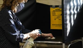 In this Oct. 22, 2020, file photo, election clerk Cheryl Lupi sanitizes a voting booth inside Haverhill City Hall during early in-person voting in Haverhill, Mass. The United States is approaching a record for the number of new daily coronavirus cases in the latest ominous sign about the disease's grip on the nation. (AP Photo/Elise Amendola, File)
