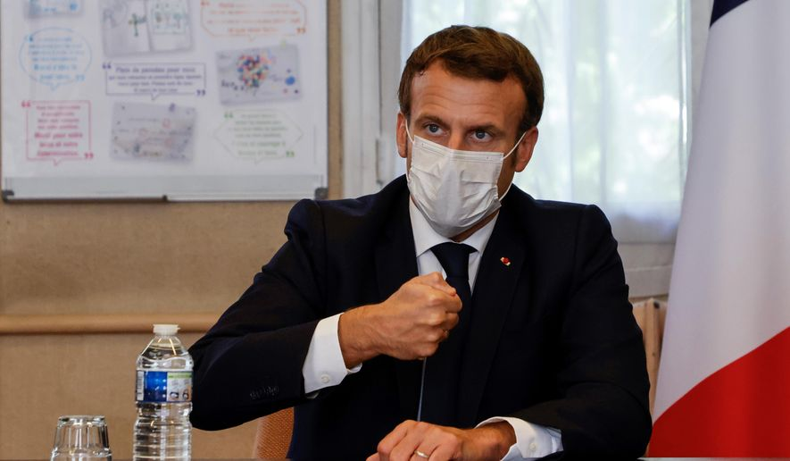 """French President Emmanuel Macron chairs a meeting with the medical staff of the Rene Dubos hospital center, in Pontoise, outside Paris, Friday Oct. 23, 2020. French Prime Minister Jean Castex said Thursday a vast extension of the nightly curfew that is intended to curb the spiraling spread of the coronavirus, saying """"the second wave is here."""" The curfew imposed in eight regions of France last week, including Paris and its suburbs, is being extended to 38 more regions and Polynesia, (Photo by Ludovic Marin, Pool via AP)"""