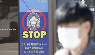 A man wearing a face mask walks past near a banner showing precaution against the coronavirus, at the Imjingak Pavilion in Paju, South Korea, Friday, Oct. 23, 2020. South Korea recorded its highest increase in coronavirus cases in more than 40 days on Friday as more infections were reported at hospitals and nursing homes. (AP Photo/Lee Jin-man)
