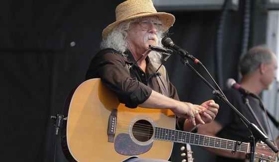 FILE - In this Aug. 15, 2020 file photo Arlo Guthrie talks during a concert at a Woodstock 50th anniversary event in Bethel, N.Y.In lengthy posts on his Facebook page and website, the 73-year-old folksinger announced Friday, Oct. 23, 2020, he is retiring from performance immediately. He's canceled numerous shows next year and says he won't book any new ones. (AP Photo/Seth Wenig, File)