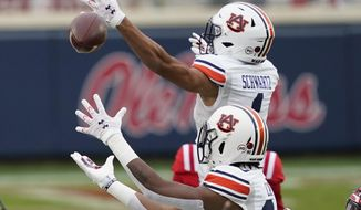 Auburn wide receivers Anthony Schwartz (1) and Ze'Vian Capers (80) both reach for an errant pass during the first half of an NCAA college football game against Mississippi in Oxford, Miss., Saturday, Oct. 24, 2020. (AP Photo/Rogelio V. Solis)