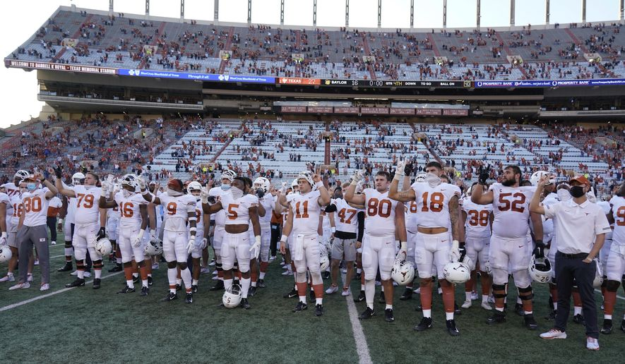 "Texas players, including Sam Ehlinger (11), sing ""The Eyes Of Texas"" after an NCAA college football game against Baylor in Austin, Texas, Saturday, Oct. 24, 2020. (AP Photo/Chuck Burton)  **FILE**"