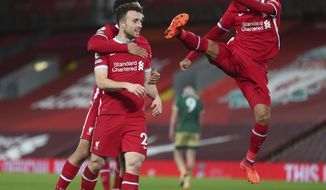 Liverpool's Diogo Jota, right, celebrates with teammate Liverpool's Trent Alexander-Arnold, behind as Liverpool's Roberto Firmino leaps in to join the clebrations after scoring his sides second goal of the game during the English Premier League soccer match between Liverpool and Sheffield United at Anfield in Liverpool, England, Saturday, Oct. 24, 2020. (Peter Byrne/Pool via AP)