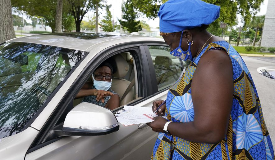 Betty George, left, signals as election worker, Caron Romain looks at her ballot at a Miami-Dade Supervisor of Elections ballot drop off site, Saturday, Oct. 24, 2020 in Miami. (AP Photo/Marta Lavandier)