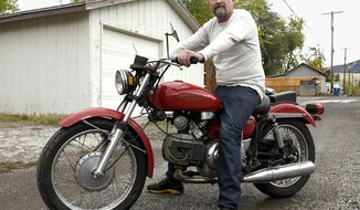 Miles McCarvel sits on his 1972 Aermacchi Harley-Davidson 350 Sprint in Missoula, Mont. on Oct. 19, 2020. The motorcycle was stolen from his garage four years ago and returned to him last week. McCarvel said he doesn't know who took the motorcycle, where it was the last four years, or who returned it and why, but the bike was in exactly the same condition as when it was stolen. (Tom Bauer/Missoulian via AP)