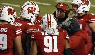 Wisconsin head coach Paul Chryst talks to his players during the first half of an NCAA college football game against Illinois Friday, Oct. 23, 2020, in Madison, Wis. (AP Photo/Morry Gash)
