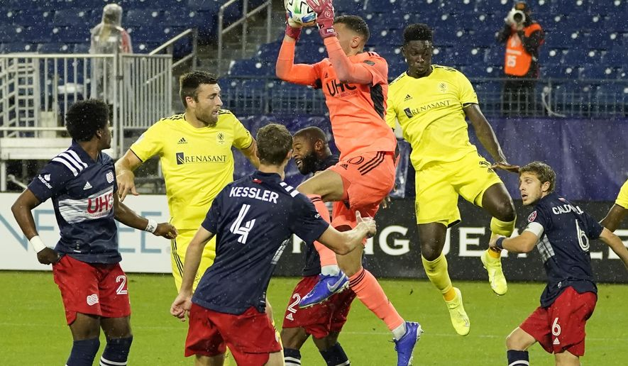 New England Revolution goalkeeper Matt Turner, center, grabs a shot in front of the goal during the first half of an MLS soccer match against Nashville SC Friday, Oct. 23, 2020, in Nashville, Tenn. (AP Photo/Mark Humphrey)