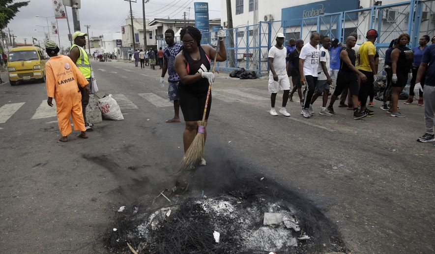 """Volunteers sweep burnt out tyres on the roads in Lagos Saturday, Oct. 24, 2020. Nigeria's president says 51 civilians have been killed in unrest following days of peaceful protests over police abuses, and he blames """"hooliganism"""" for the violence while asserting that security forces have used """"extreme restraint.""""(AP Photo/Sunday Alamba)"""