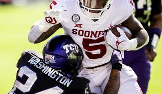 Oklahoma running back T.J. Pledger (5) scores a touchdown as TCU safety Ar'Darius Washington (24) defends during the first half of an NCAA College football game, Saturday, Oct. 24, 2020, in Fort Worth, Texas. (AP Photo/Brandon Wade)