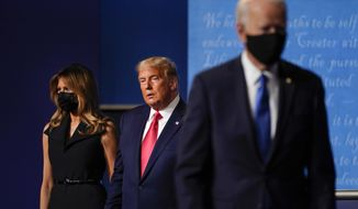 First lady Melania Trump, left, and President Donald Trump, center, remain on stage as Democratic presidential candidate former Vice President Joe Biden, right, walks away at the conclusion of the second and final presidential debate Thursday, Oct. 22, 2020, at Belmont University in Nashville, Tenn. (AP Photo/Julio Cortez)