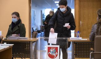 A Lithuanian woman, wearing face masks to protect against coronavirus, casts her ballot at a polling station during early voting in the second round of a parliamentary election in Vilnius, Lithuania, Thursday, Oct. 22, 2020. Lithuanians will vote in the second round of a parliamentary election on upcoming Sunday during the rise in the incidence of coronavirus infection in the country. (AP Photo / Mindaugas Kulbis)
