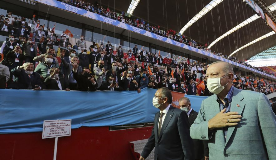 Turkey's President Recep Tayyip Erdogan, right, wearing a mask to help protect against the spread of coronavirus, greets his ruling party members gathered in a stadium, in Kayseri, Turkey, Saturday, Oct. 24, 2020. Turkey's Health Minister Fahrettin Koca said Friday COVID-19 infections were on the rise across the country and 40 percent of cases were in Istanbul, Turkey's most populous city with more than 15 million people.(Turkish Presidency via AP, Pool)
