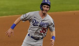 Los Angeles Dodgers' Cody Bellinger scores on a bunt by Austin Barnes during the fourth inning in Game 3 of the baseball World Series against the Tampa Bay Rays Friday, Oct. 23, 2020, in Arlington, Texas. (AP Photo/Tony Gutierrez)