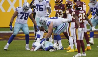 Dallas Cowboys offensive guard Connor McGovern (66) leans down to check on teammate quarterback Andy Dalton (14) who lays on the ground after a late hit by Washington Football Team inside linebacker Jon Bostic (53) in the second half of an NFL football game, Sunday, Oct. 25, 2020, in Landover, Md. Dalton left the field after play and Bostic was ejected from the game.(AP Photo/Susan Walsh)