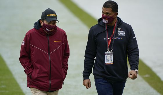 Washington Football Team owner Dan Snyder, left, and team president Jason Wright, right, walk off the field before the start of the first half of an NFL football game against Dallas Cowboys, Sunday, Oct. 25, 2020, in Landover, Md. (AP Photo/Susan Walsh) ** FILE **
