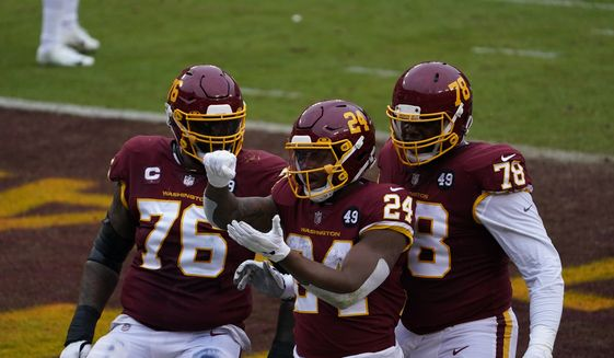 Washington Football Team running back Antonio Gibson (24) celebrating his touchdown with teammates offensive tackle Morgan Moses and offensive tackle Cornelius Lucas (78)x in the first half of an NFL football game, Sunday, Oct. 25, 2020, in Landover, Md. (AP Photo/Susan Walsh)
