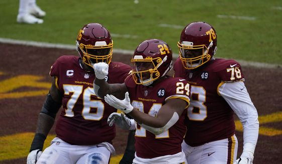 Washington Football Team running back Antonio Gibson (24) celebrating his touchdown with teammates offensive tackle Morgan Moses and offensive tackle Cornelius Lucas (78)x in the first half of an NFL football game, Sunday, Oct. 25, 2020, in Landover, Md. (AP Photo/Susan Walsh) **FILE**
