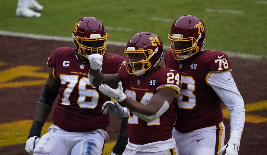 Washington Football Team running back Antonio Gibson (24) celebrating his touchdown with teammates offensive tackle Morgan Moses and offensive tackle Cornelius Lucas (78) in the first half of an NFL football game, Sunday, Oct. 25, 2020, in Landover, Md. (AP Photo/Susan Walsh) ** FILE **