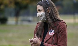 U.S. Rep. Alexandria Ocasio-Cortez, (D-N.Y.) waits to meet supporters and campaign volunteers at a Pledge to Vote event, Sunday, Oct. 25, 2020, in the Bronx borough of New York. (AP Photo/Kathy Willens)