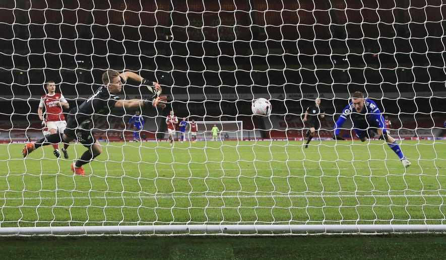 Leicester's Jamie Vardy, right, heads the ball past Arsenal's goalkeeper Bernd Leno to score his team's goal during the English Premier League soccer match between Arsenal and Leicester City at Emirates Stadium in London, England, Sunday, Oct. 25, 2020. (Catherine Ivill/Pool via AP)