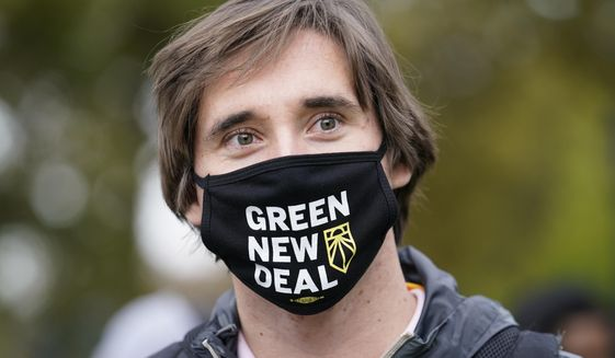A volunteer working for U.S. Rep. Alexandria Ocasio-Cortez, (D-N.Y.), wears a Green New Deal mask as he waits in line to meet the New York congresswoman at a Pledge to Vote event, Sunday, Oct. 25, 2020, in the Bronx borough of New York. Early voting ahead of the Nov. 3 general election continued for the second day in New York state. (AP Photo/Kathy Willens)