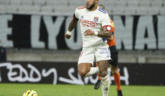 Lyon's Memphis Depay controls the ball during the French League One soccer match between Lyon and Monaco at Groupama stadium in Decines, near Lyon, central France, Sunday, Oct. 25, 2020. (AP Photo/Laurent Cipriani)