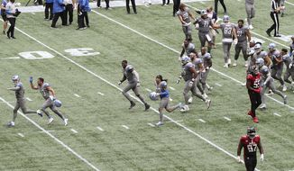 Detroit Lions kicker Matt Prater, far left, is chased off the field by celebrating teammates after making the extra point attempt to defeat the Atlanta Falcons as time expired in an NFL football game while Falcons players Grady Jarrett, bottom right, and Steven Means walk off the field Sunday, Oct. 25, 2020, in Atlanta. (Curtis Compton/Atlanta Journal-Constitution via AP)