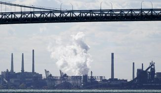 Zug Island, a heavily industrialized island at the southern city limits of Detroit is seen, Friday, Oct. 16, 2020, in Detroit. The area in Southwest Detroit has been the subject of numerous air pollution and public health studies. The area has a refinery, a coal-fired power plant, steel mills and other industrial sites. (AP Photo/Carlos Osorio)