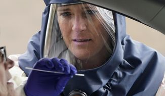In this Friday, Oct. 23, 2020, photo, Salt Lake County Health Department public health nurse Lee Cherie Booth performs a coronavirus test outside the Salt Lake County Health Department in Salt Lake City. (AP Photo/Rick Bowmer) **FILE**
