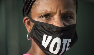 "Caprice Clipps wears a ""vote"" mask as she waits outside the Smoothie King Center in New Orleans for one of the last days of early voting on Monday, Oct. 26, 2020, for one of the last days of early voting. (Chris Granger/The Advocate via AP)"