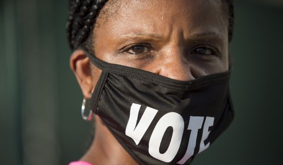 """Caprice Clipps wears a """"vote"""" mask as she waits outside the Smoothie King Center in New Orleans for one of the last days of early voting on Monday, Oct. 26, 2020, for one of the last days of early voting. (Chris Granger/The Advocate via AP)"""