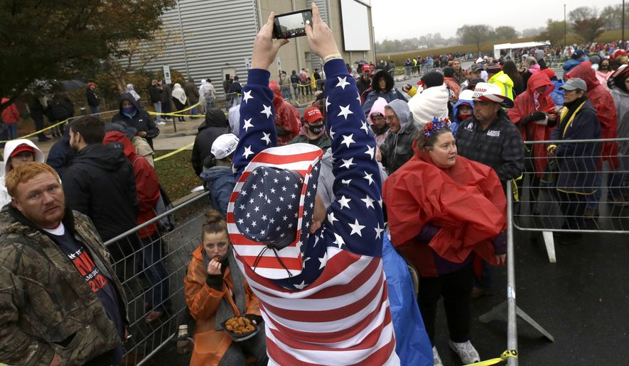 A supporter of President Donald Trump photographs the gathering crowd before a campaign rally at Lancaster Airport, Monday, Oct. 26, 2020 in Lititz, Pa. (AP Photo/Jacqueline Larma)