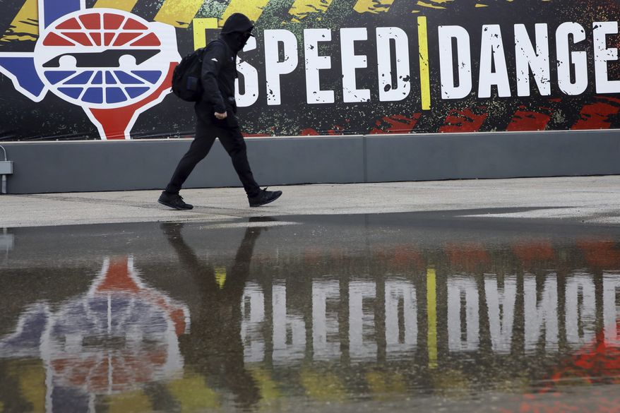 A pit crew member walks past the media center as crews wait out a delay at a NASCAR Cup Series auto race after morning rain prevented the 9 a.m. rescheduled start at Texas Motor Speedway in Fort Worth, Texas, Monday, Oct. 26, 2020. (AP Photo/Richard W. Rodriguez)