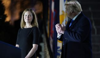 President Donald Trump looks toward Amy Coney Barrett, before Supreme Court Justice Clarence Thomas administers the Constitutional Oath to her on the South Lawn of the White House in Washington, Monday, Oct. 26, 2020, after Barrett was confirmed by the Senate earlier in the evening. (AP Photo/Patrick Semansky)