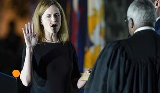 Supreme Court Justice Clarence Thomas administers the Constitutional Oath to Amy Coney Barrett on the South Lawn of the White House in Washington, Monday, Oct. 26, 2020, after Barrett was confirmed by the Senate earlier in the evening. Jesse Barrett holds the Bible. (AP Photo/Patrick Semansky)