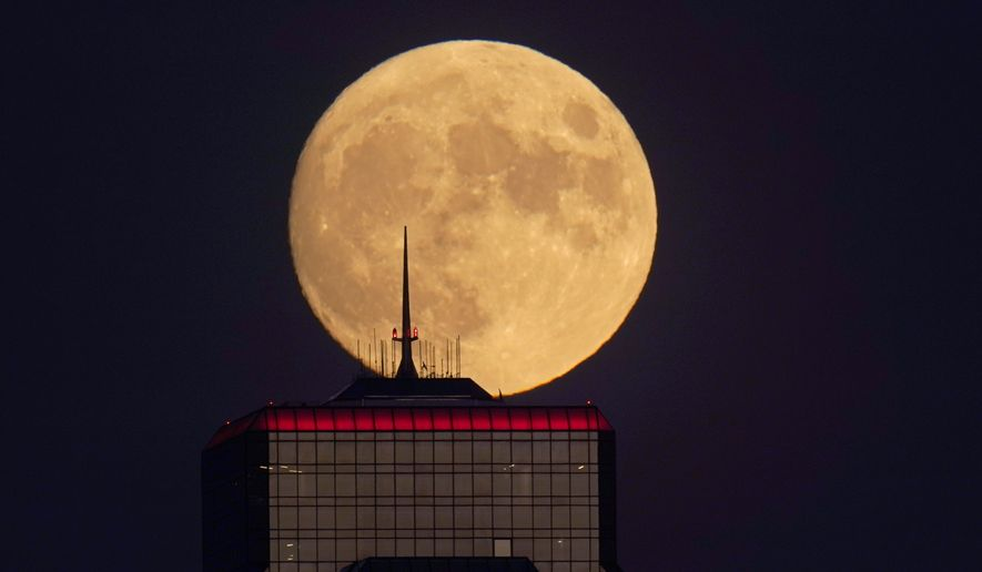 In this Wednesday, Sept. 30, 2020, file photo, a nearly full moon rises, with an office building in the foreground, in downtown Kansas City, Mo. The moons shadowed, frigid nooks and crannies may hold frozen water in more places and in larger quantities than previously suspected, good news for astronauts at future lunar bases who could tap into these resources for drinking and making rocket fuel, scientists reported Monday, Oct. 26, 2020. (AP Photo/Charlie Riedel, File)