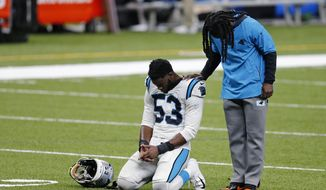 Carolina Panthers defensive end Brian Burns (53) pauses for a moment of silence as he walks off the field after an NFL football game against the New Orleans Saints in New Orleans, Sunday, Oct. 25, 2020. The Saints won 27-24. (AP Photo/Brett Duke)
