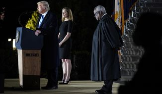 President Donald Trump speaks as Amy Coney Barrett looks on, before Supreme Court Justice Clarence Thomas, right, administers the Constitutional Oath to her on the South Lawn of the White House in Washington, Monday, Oct. 26, 2020, after Barrett was confirmed by the Senate earlier in the evening. (AP Photo/Patrick Semansky)