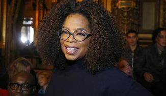 """FILE - Oprah Winfrey arrives for the presentation of Stella McCartney's ready-to-wear Fall-Winter 2019-2020 fashion collection in Paris on March 4, 2019. Winfrey is setting aside her usual book club recommendations and instead citing seven personal favorites ranging from James Baldwin's landmark essays in """"The Fire Next Time"""" to Mary Oliver's poetry collection """"Devotions."""" She is calling her choices """"The Books That See Me Through,"""" works she values for """"their ability to comfort, inspire, and enlighten"""" her. (AP Photo/Michel Euler, File)"""