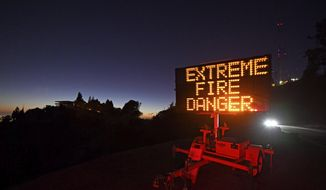 A roadside sign warns motorists of extreme fire danger on Grizzly Peak Boulevard, in Oakland, Calif., Sunday, Oct. 25, 2020. Due to high winds and dry conditions PG&E will turn off the power to over 361,000 customers in 36 counties to protect them from possible wildfires caused by downed power lines. The National Weather Service predicts offshore winds from the north peaking at higher elevations up to 70 mph. (Jose Carlos Fajardo/Bay Area News Group via AP)