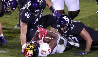 Maryland running back Peny Boone (13) is tackled by Northwestern defensive line Devin O'Rourke, left, and linebacker Troy Hudetz during the second half of an NCAA college football game in Evanston, Ill., Saturday, Oct. 24, 2020. (AP Photo/Nam Y. Huh)