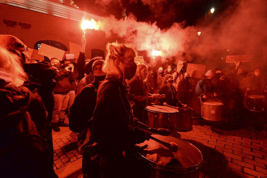 People protest against imposing further restrictions on abortion law in front of the Presidential palace in Warsaw, Poland, Sunday, Oct. 25, 2020. (AP Photo/Czarek Sokolowski)