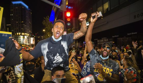 In this Oct. 11, 2020, file photo, fans in Los Angeles celebrate after the Los Angeles Lakers defeated the Miami Heat in Game 6 of basketball's NBA Finals to win the championship. A backlog in coronavirus testing results hid a recent rise in infections in Los Angeles County, the county's top health official said Monday, Oct. 26, 2020, warning that fans gathering to watch recent championship sporting events may have increased the spread. (AP Photo/Jintak Han, File)  **FILE**