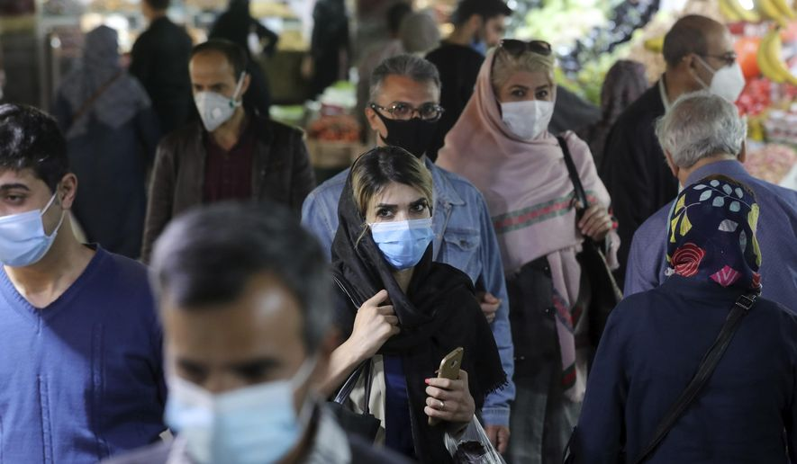 FILE - In this Oct. 15, 2020, file photo, people wear protective face masks to help prevent the spread of the coronavirus in the Tajrish traditional bazaar in northern Tehran, Iran. As a new wave of coronavirus infections engulfed Iran this month, filling hospitals and driving up the death toll, the country's health minister gave a rare speech criticizing the government's powerlessness to enforce basic health measures. (AP Photo/Ebrahim Noroozi, File)