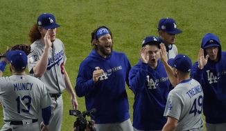 Los Angeles Dodgers starting pitcher Clayton Kershaw, center, celebrates after their win against the Tampa Bay Rays in Game 5 of the baseball World Series Sunday, Oct. 25, 2020, in Arlington, Texas. Dodgers beat the Rays 4-2 to lead the series 3-2 games. (AP Photo/Sue Ogrocki)  **FILE**