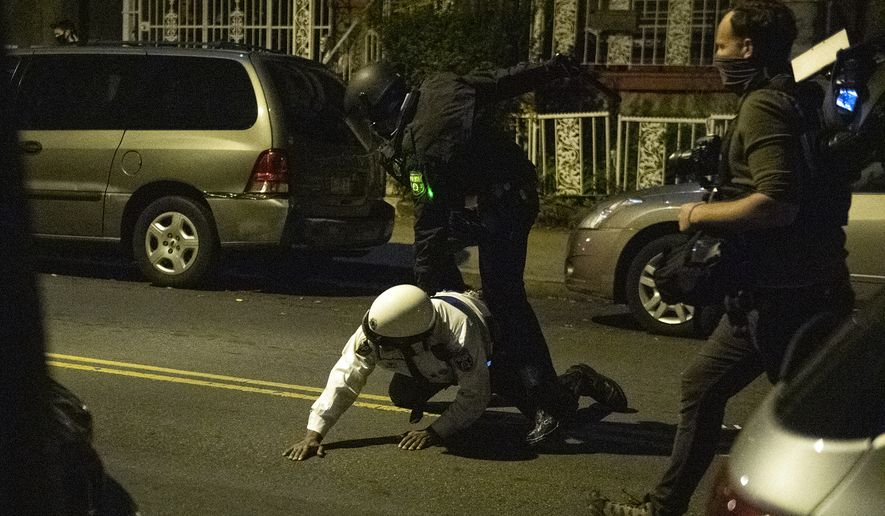 A police officer goes down attempting to tackle a demonstrator during protests Tuesday, Oct. 27, 2020, in Philadelphia, the day after Walter Wallace Jr., a Black man, was fatally shot by Philadelphia police. (Joe Lamberti/Camden Courier-Post via AP)