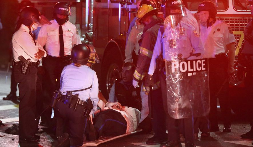 A police officer lies on the ground before being loaded into an ambulance on 52nd Street in West Philadelphia in the early hours of Tuesday, Oct. 27, 2020. Protesters gathered after police shot and killed a Black man in West Philadelphia on Monday. (Tim Tai/The Philadelphia Inquirer via AP)