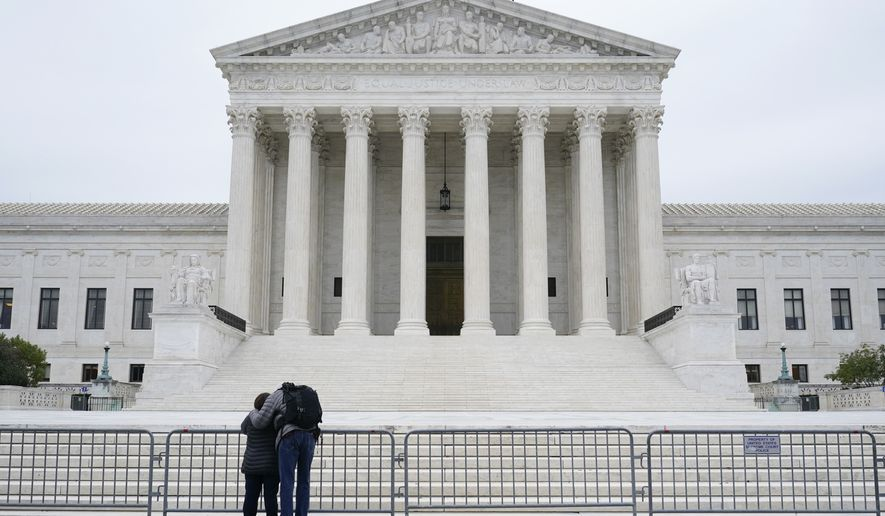A woman and man pray outside the Supreme Court on Capitol Hill in Washington, Tuesday, Oct. 27, 2020, the day after the Senate confirmed Amy Coney Barrett to become a Supreme Court Justice. (AP Photo/Patrick Semansky)