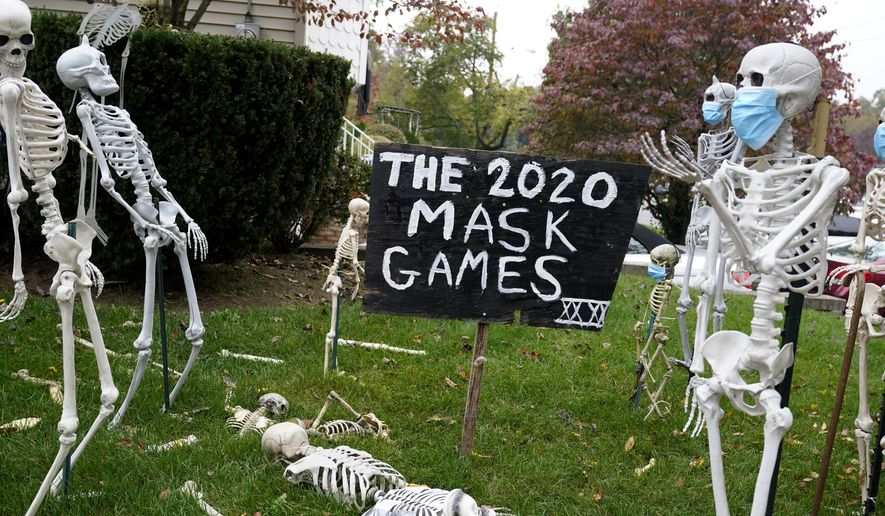 In this Oct. 22, 2020, file photo, coronavirus-themed Halloween decorations are displayed on a lawn in Tenafly, N.J. In a year when fear and death have commandeered front-row seats in American life, what does it mean to encounter Halloween, a holiday whose very existence hinges on turning fear and death into entertainment? (AP Photo/Seth Wenig, File)